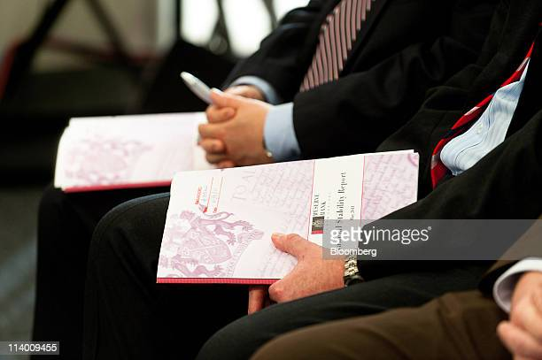 Reserve Bank of New Zealand employees hold copies of the NZ Financial Stability Report during a news conference at the central bank in Wellington New...