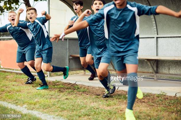 reserve players celebrate a goal scored by their team. - reserve athlete stock pictures, royalty-free photos & images