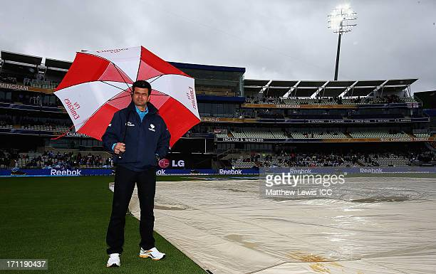Reserve Umpire Aleem Dar looks on as rain delays the start of play ahead of the ICC Champions Trophy Final between England and India at Edgbaston on...