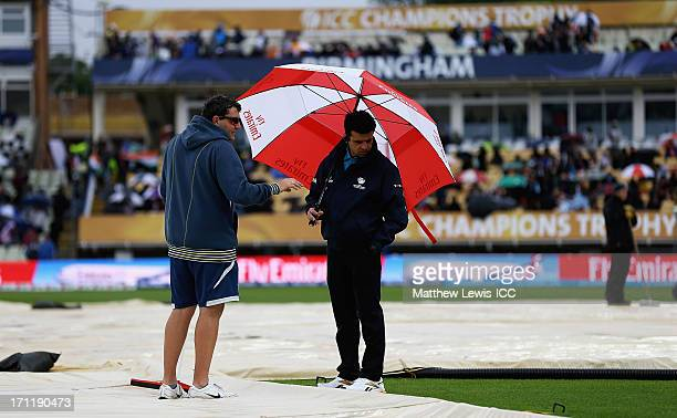 Reserve Umpire Aleem Dar talks to groundsman Gary Barwell as rain delays the start of play ahead of the ICC Champions Trophy Final between England...