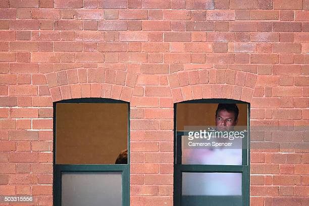 Reserve umpire Mick Martell looks out the window at the rain as play is suspended during day two of the third Test match between Australia and the...