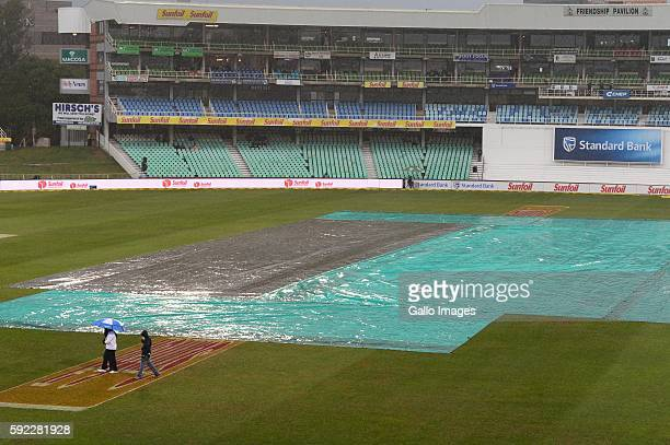 Reserve umpire Shaun George walk off as the rain falls during day 2 of the 1st Sunfoil International Test match between South Africa and New Zealand...