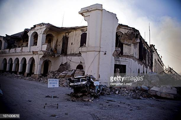 """Reserved parking"""" sign is use to block a road outside the Haitian National Bank by guards protecting its damaged vault and cash reserves. On January..."""