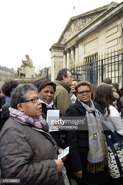Resettled children from La Reunion stand on February 18 2014 outside the National Assembly in Paris on the day the Parliament is to debate a bill...