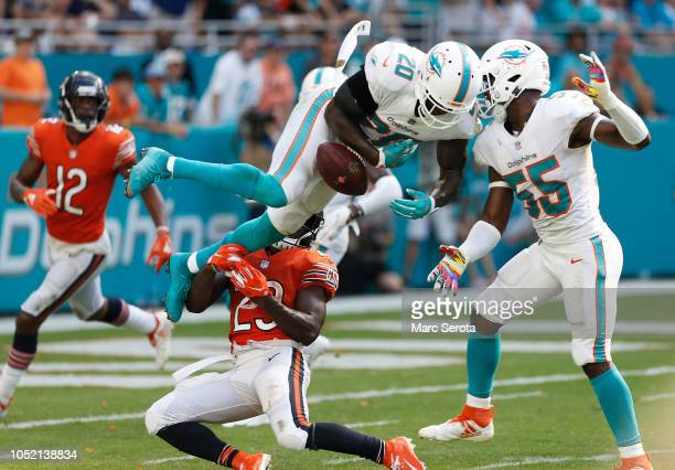 Reshad Jones and Jerome Baker of the Miami Dolphins collide as Kyle Fuller of the Chicago Bears defends in the second half of the game at Hard Rock...
