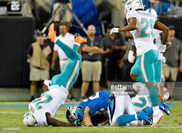 Reshad Jones of the Miami Dolphins dives over Christian McCaffrey of the Carolina Panthers in the second quarter during the game at Bank of America...
