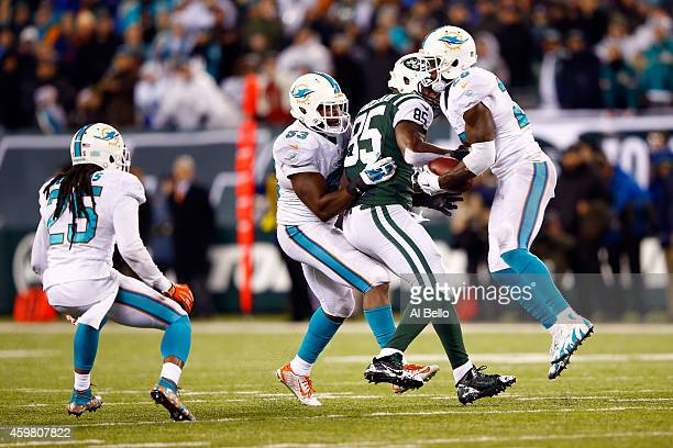 Reshad Jones of the Miami Dolphins intercepts a ball intended for Jeff Cumberland of the New York Jets late in the fourth quarter during their game...