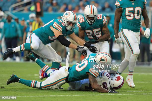 Reshad Jones of the Miami Dolphins tackles Marcus Murphy of the Buffalo Bills during the second quarter at Hard Rock Stadium on December 31 2017 in...