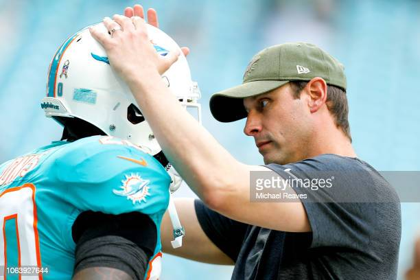 Reshad Jones talks with head coach Adam Gase of the Miami Dolphins prior to the game against the New York Jets at Hard Rock Stadium on November 4...
