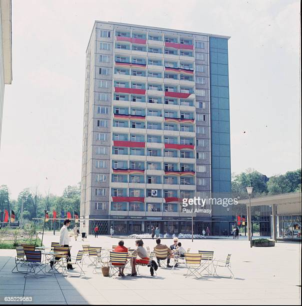"""Residence building in East Berlin, type """"HLM"""". Banners hang from the balconies, alternating red and the colors and symbol of the East German flag."""