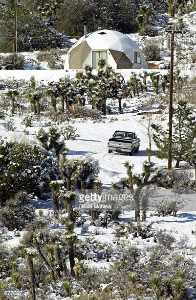 A residence standing among joshua trees in the desert near Pinon Hills CA is covered with snow January 28 as a storm moves out of southern California...