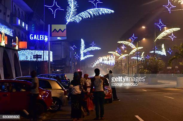 Residenst enjoy an evening stroll on December 29 2016 in the business district of Plateau d'Abidjan decorated for Chrismas and New Year's...