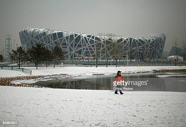 Resident admires the Bird's Nest in the snow on February 18, 2009 in Beijing, China's capital embraced the first snowfalls of 2009, following the...