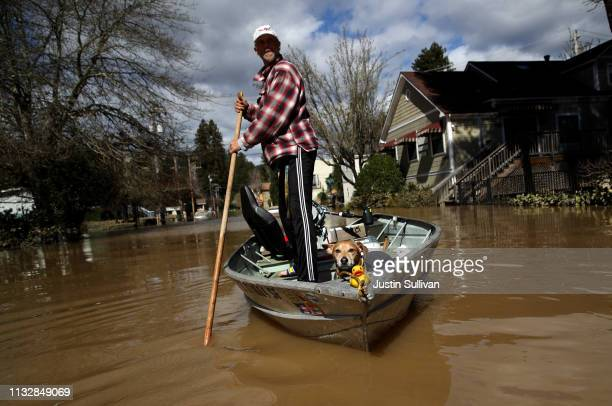 A resident and his dog navigate through a flooded neighborhood on February 28 2019 in Guerneville California The Russian River has crested over flood...