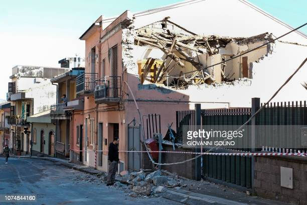 A resident assesses damages after a house's roof collapsed on a street in Zafferana Etnea near Catania on December 26 after a 48magnitude earthquake...