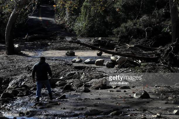 A resident attempts to cross a road that was damaged by a mudslide on January 10 2018 in Montecito California 15 people have died and hundreds are...