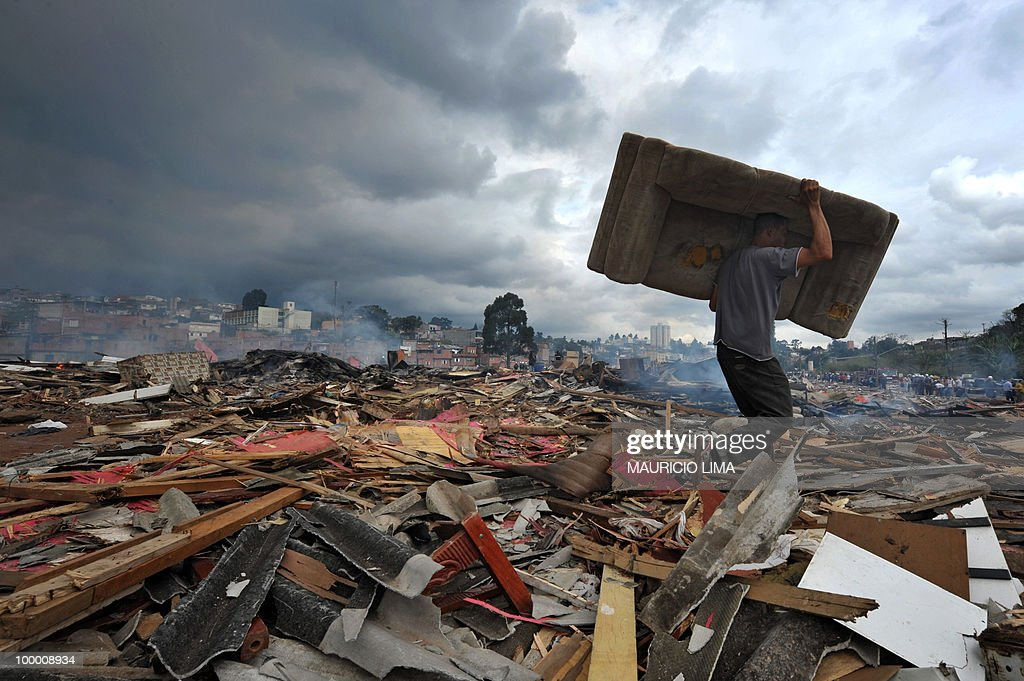 A resident attempts to save his belongings during an eviction at Capao Redondo shantytown, southern outskirts of Sao Paulo, Brazil, on August 24, 2009. Residents set huts on fire as a way to protest. Almost 800 families (some 1200 people) were removed from their huts in a huge area which was illegaly occupied by them since 2007. AFP PHOTO/Mauricio LIMA
