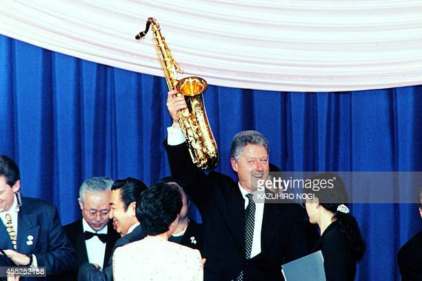 resident Bill Clinton shows off a brand new saxophone given by Japanese jazz musician Sadao Watanabe at a luncheon hosted by Prime Minister Ryutaro...