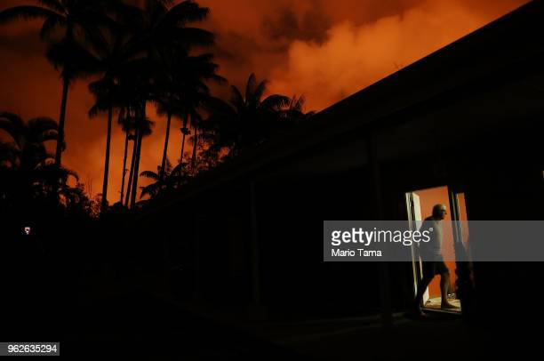 Resident Bill Hubbard enters his home as lava from a Kilauea volcano fissure illuminates the sky in Leilani Estates on Hawaii's Big Island on May 25...