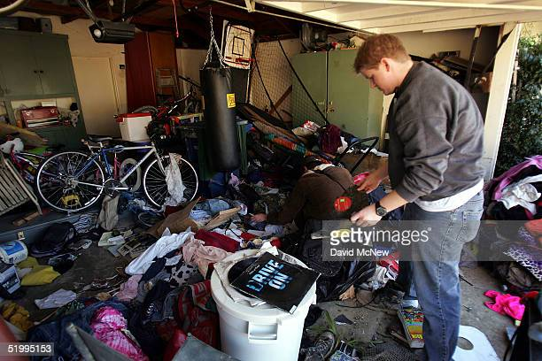 Resident Brandon Lindauer helps his neighbors sort through scattered belongings found after the deadly mudslide that killed at least 10 people on the...