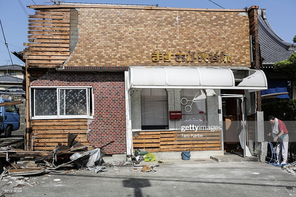 A resident brushes his teeth at his damaged beauty salon after an earthquake on April 15, 2016 in Mashiki, Kumamoto, Japan. At least nine people have died in a powerful earthquake, with a preliminary magnitude of 6.4, that struck Kumamoto Prefecture yesterday.