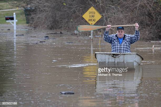 A resident canoes himself down a street submerged in floodwater from the Meremac River on December 30 2015 in Arnold Missouri The St Louis area and...