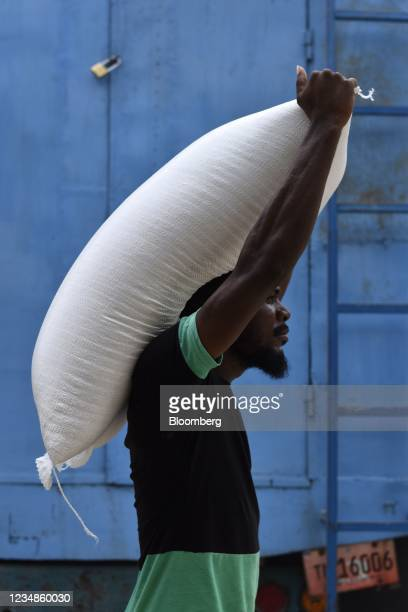 Resident carries a bag of rice while leaving a World Food Programme distribution site in Port-Salut, Haiti, on Tuesday, Aug. 24, 2021. Haiti's...