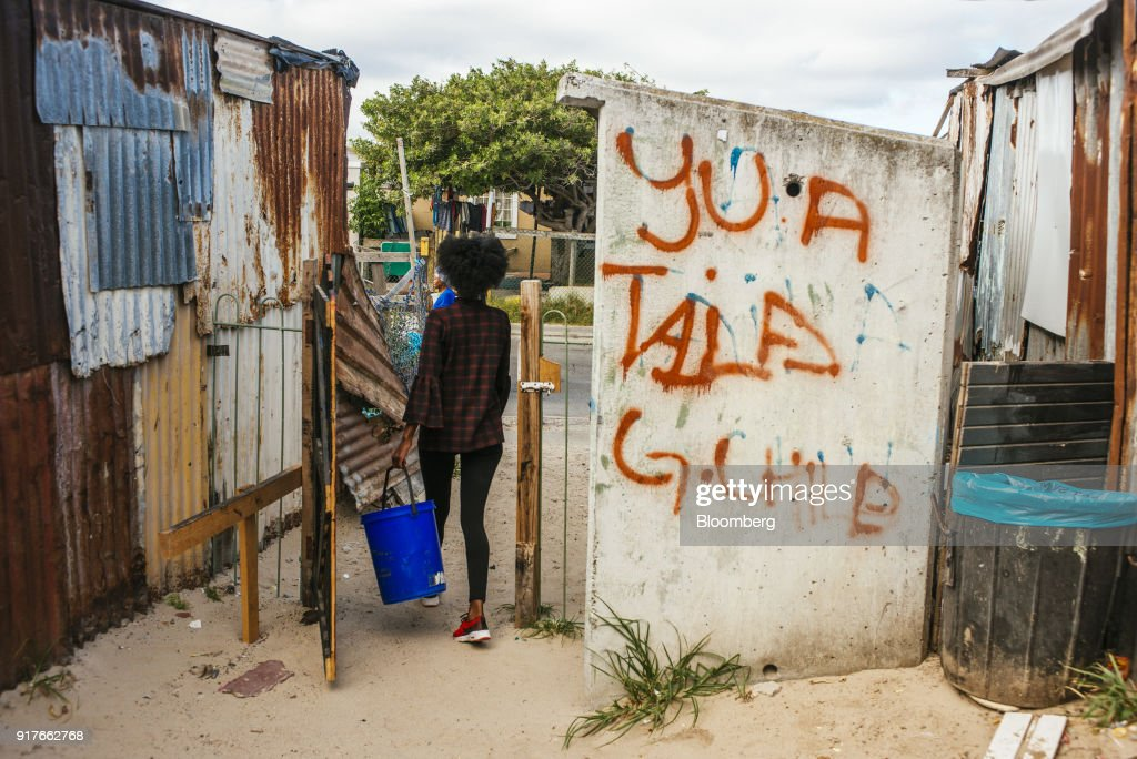 A resident carries a plastic container filled with water from a communal tap back to her home in the Khayelitsha township, Cape Town, South Africa, on Friday, Feb. 9, 2018. Confronted by the worst drought on record after years of disastrously low rainfall, city authorities say they may have to turn off the water entirely on May 11, the famous 'Day Zero,' if reservoir levels keep falling and consumption doesn't slow enough. Photographer: Waldo Swiegers/Bloomberg via Getty Images
