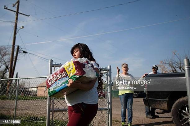 Resident carries drinking water distributed by Donna Johnson who distributes drinking water to neighbors as water wells supplying hundreds of...
