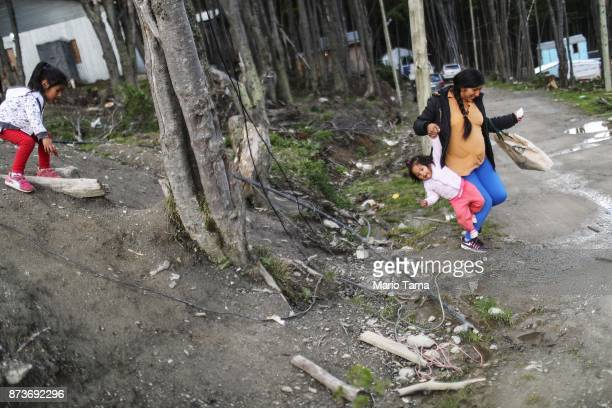 A resident carries her daughter downhill at an informal mountainside community whose residents depend on runoff water from the receding Martial...