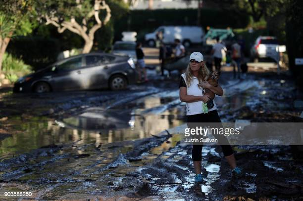 A resident carries her dog as she walks on a mud covered road after a mudslide on January 10 2018 in Montecito California 17 people have died and...