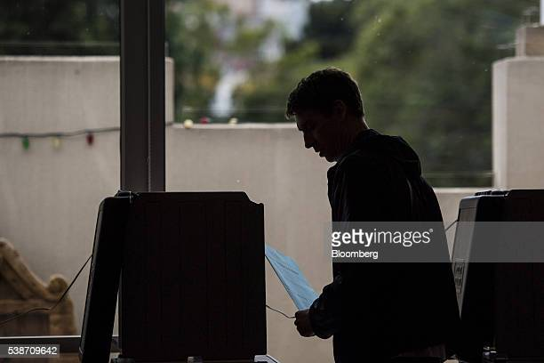 A resident carries his ballot during the presidential primary election in San Francisco California US on Tuesday June 7 2016 Hillary Clinton secured...