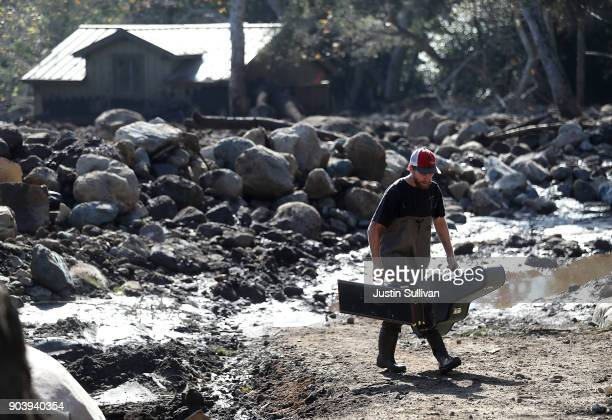 A resident carries items that he salvaged from the home of a family member that was destroyed by a mudslide on January 11 2018 in Montecito...