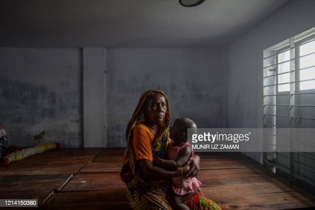 A resident carrying a child rests in a shelter ahead of the expected landfall of cyclone Amphan in Dacope of Khulna district on May 20 2020 Several...
