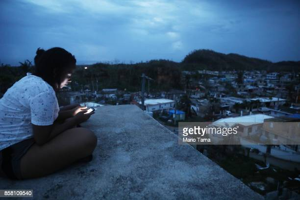 A resident checks her cell phone on her rooftop at dusk about two weeks after Hurricane Maria swept through the island on October 5 2017 in San...