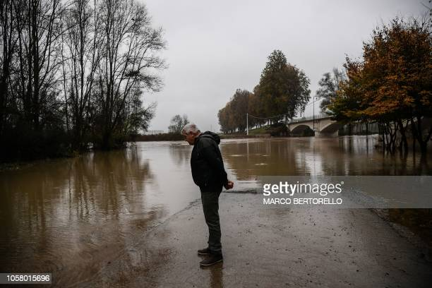 A resident checks the level of the Po river on November 6 2018 in Carde southwest of Turin after it rose overnight following heavy rain Rains and...