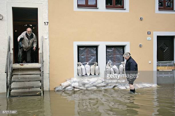 Resident Christine Mokrzki stands in front of the house of her son in the flooded streets of the eastern German city of Pirna next to the river Elbe...