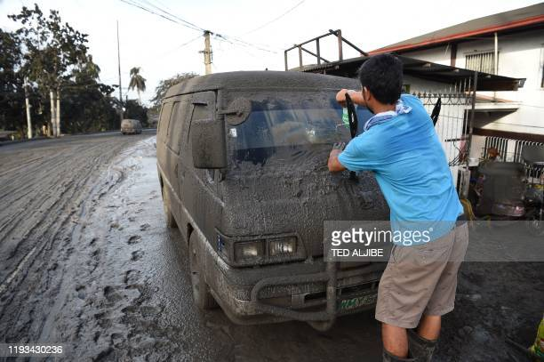 A resident cleans mud and ash from his car after Taal volcano began spewing ash over Tanauan town Batangas province south of Manila on January 13...