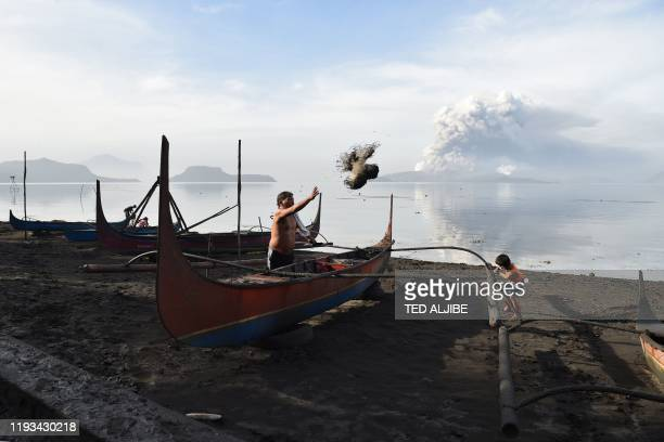TOPSHOT A resident cleans mud and ash from his outrigger canoe after Taal volcano began spewing ash over Tanauan town Batangas province south of...