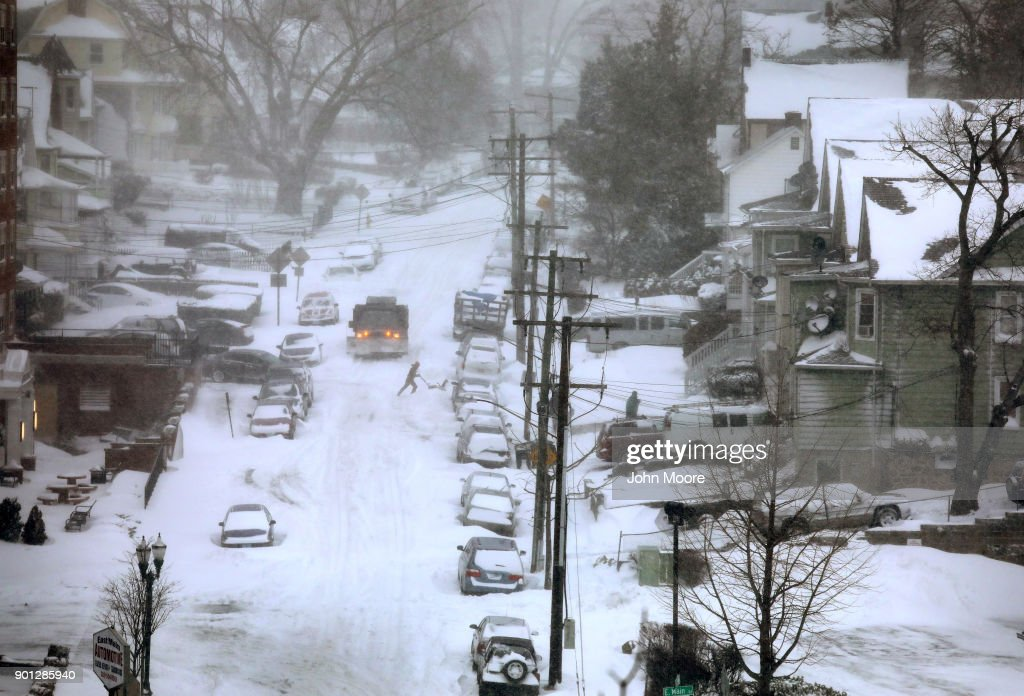 A resident clears snow from in front of his house on January 4, 2018 in Stamford, Connecticut. The 'bomb cyclone' dumped heavy snows in New England as the storm system moved up the U.S. east coast.