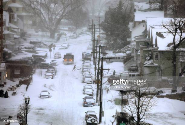 A resident clears snow from in front of his house on January 4 2018 in Stamford Connecticut The bomb cyclone dumped heavy snows in New England as the...