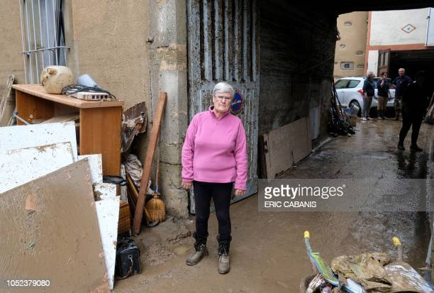 Resident Clotilde Robert poses for a photograph in front of her home as residents clear the debris from their homes and shops following earlier...