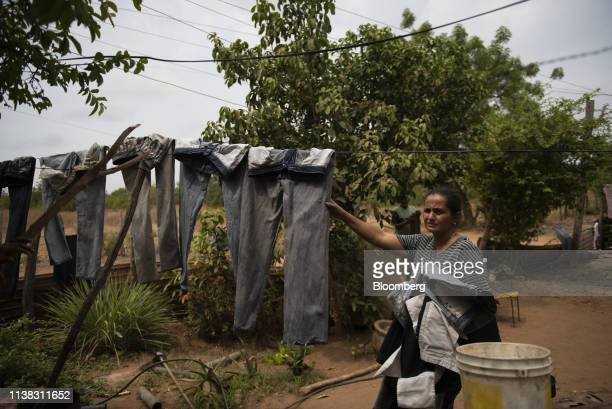 A resident collects dried laundry in Maracaibo Zulia state Venezuela on Tuesday April 16 2019 Maracaibo residents are still struggling without water...