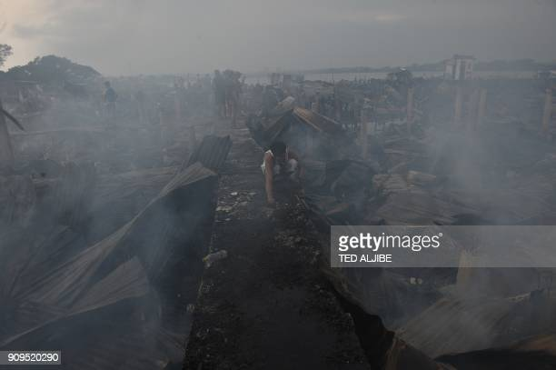 A resident collects recyclable materials amongst destroyed homes after a fire broke out at an informal settlers area beside the coast in Bacoor town...