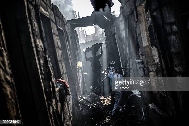 A resident collects scrap metal from the rubble of burnt shanties after a fire gutted a residential area in Caloocan city north of Manila Philippines...