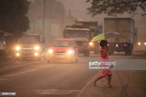 A resident covers her face from ashfall after Mount Mayon shot up a giant mushroomshaped cloud as it continues to erupt in Ligao town near Legazpi...