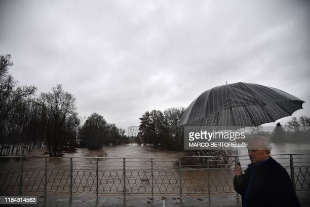A resident crosses a bridge above the Po river in the village of Carde south of Turin after the river overflew its banks following heavy rainfall on...