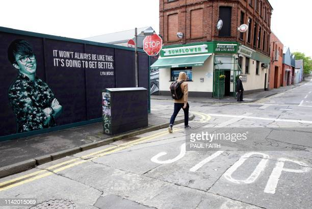 A resident cycles past a newly painted mural featuring murdered journalist Lyra McKee whose death sparked a new round of political talks chaired by...