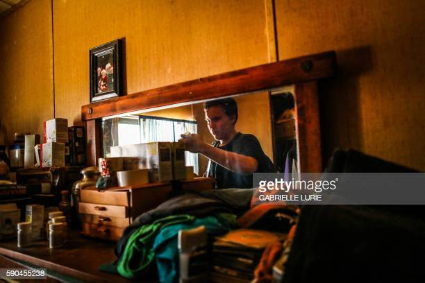 Resident Daniel Brown is reflected in the mirror as he holds a bottle of anxiety pills he is retrieving for his grandfather during his first visit to...