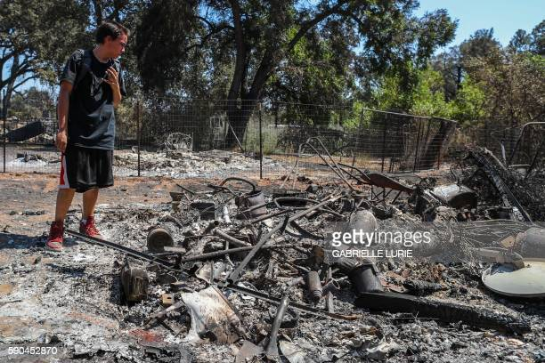 Resident Daniel Brown speaks on his phone to his mother as he inspects damage to his shed in the Clayton Fire in Lower Lake California August 16 2016...